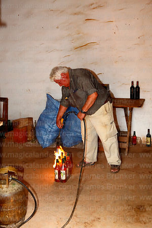 Don Tomas sealing a pack of bottles of ratafia with a homemade gas blow torch in his bodega, Villa Abecia, Chuquisaca Department, Bolivia