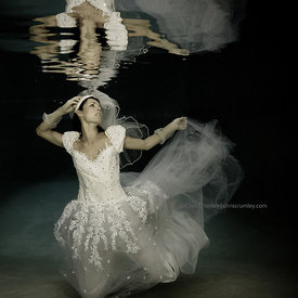 Model Virginie Leplus in white wedding dress underwater in pool