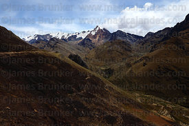 Hillside burnt by fire started by peasants to clear vegetation , Mt Akamani in background , Cordillera Apolobamba , Bolivia