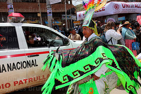 Waca waca dancer in bull costume looking at policewoman in patrol car, Virgen de la Candelaria festival, Puno, Peru
