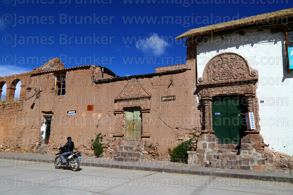 Man riding motorbike past doorways of Casa de la Inquisición, Plaza de Armas, Juli, Puno Region, Peru