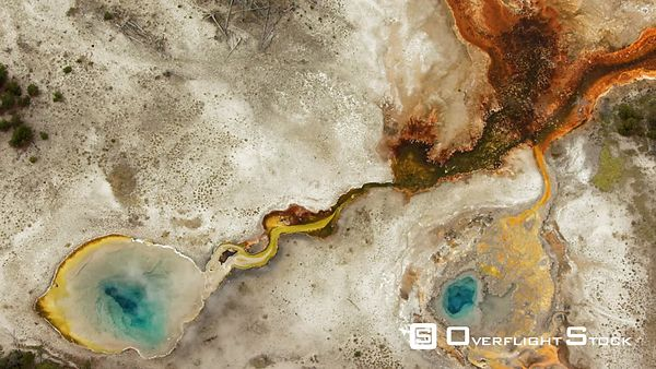 A pair of colorful thermal pools sit next to the Firehole River in the Upper Geyser Basin of Yellowstone National Park