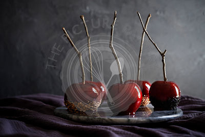 Marble tray of beautiful, red, candy apples on dark purple linen. Moody feel with dark textured background.