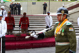 A military police officer wearing an old German style pickelhaube spiked helmet parades past the remains of Eduardo Abaroa, Plaza Avaroa, La Paz, Bolivia