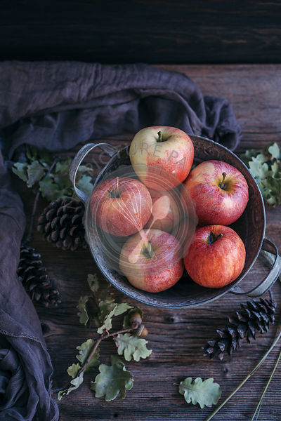 Red apples in a bucket on a rustic wooden table