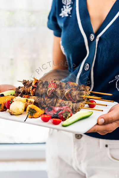 A woman serving lamb shish kebabs with grilled peppers, shallots, fresh cherry tomatoes and cucumber on a white marble board photographed from front view.