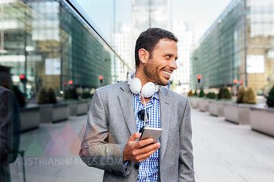 Smiling businessman with headphones and cell phone in the city
