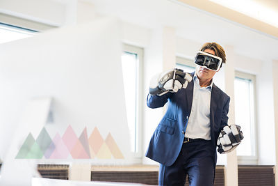 Businessman wearing VR glasses and ice hockey gloves in office