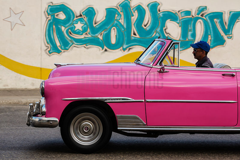 Pink Vintage American Car in Front of Revolutionary Graffiti