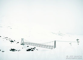Metal bridge for hikers in snow landscape