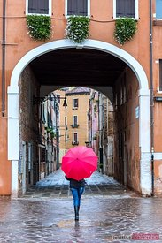 Woman with red umbrella walking in a small alley