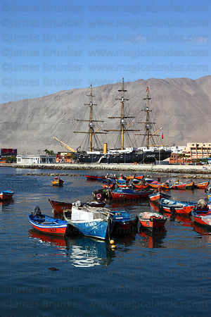 Fishing boats in port , Esmeralda frigate in background , Iquique , Chile
