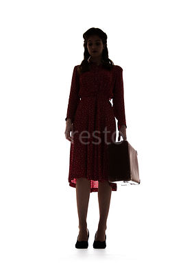 A silhouette of a 1940's woman in a red dress, walking with a suitcase – shot from low-level.