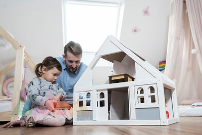 Father and toddler daughter playing with doll house in her nursery