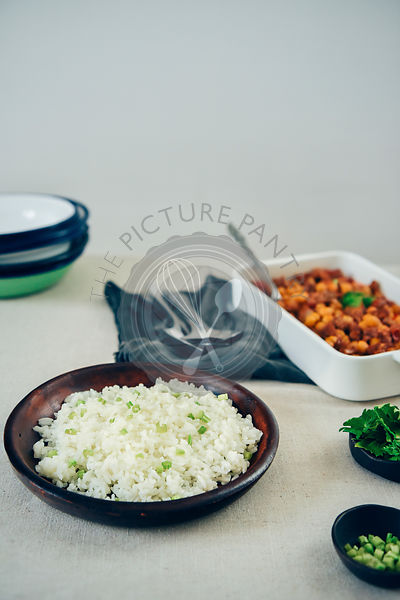 Simple fried rice in a dark ceramic dish on a dinner table photographed from front view. Herbs in small bowls, spoons, a casserole pan and bowls accompany.