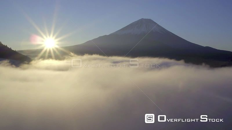 Aerial shot at sunrise tracking over clouds above Lake Shoji, with Mount Fuji in the background, Fuji Hazone Izu National Park, Japan, November 2017.