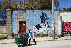 Woman pushing drinks cart past cholita mural on wall, Uyuni, Bolivia