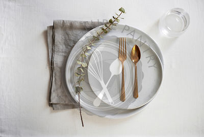 A beautiful, minimal table setting with organic, handmade gray plates, gold flatware and a natural linen.