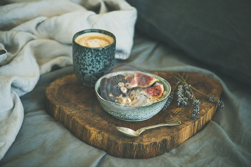 Rice coconut porridge with figs, berries and hazelnuts and cup of coffee over rustic wooden board background