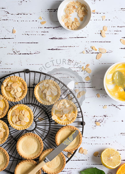Small round lemon tarts being filled with lemon butter and decorated with toasted almond flakes.