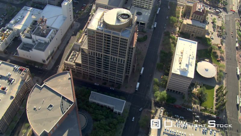 Diagonal flight over downtown Phoenix skyscrapers, looking down onto streets.