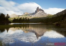 Mountain peak reflected in apline lake in summer Dolomites Italy