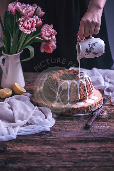 Woman drizzling lemon glaze over a bundt cake