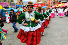 Cholita wearing an emoji face purse dancing during parades for the Entierro del Pepino, La Paz, Bolivia