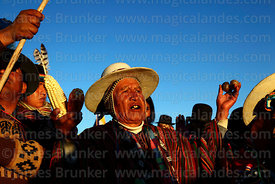 Aymara leader holding up maize and potatos as offerings at sunrise during Aymara New Year celebrations, Tiwanaku, Bolivia