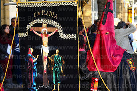 Penitent with banner of Brotherhood of Jesus on the cross / Paso del Calvario during Good Friday procession, La Paz, Bolivia