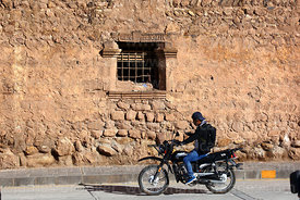 Man riding motorbike past window of Casa de la Inquisición, Plaza de Armas, Juli, Puno Region, Peru