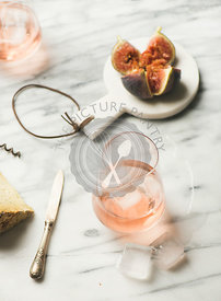 Glass of rose wine, fresh figs and cheese, selective focus