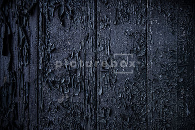 A background textured image of burnt wood.