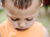 Three year old boy looking down