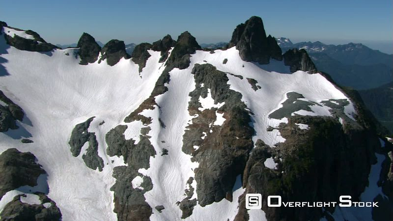 Low flight over snowfields of jagged peak in British Columbia, Canada