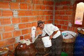 Man pouring chicha / maize beer from ceramic storage urn into plastic bucket for serving, near Tarija, Bolivia
