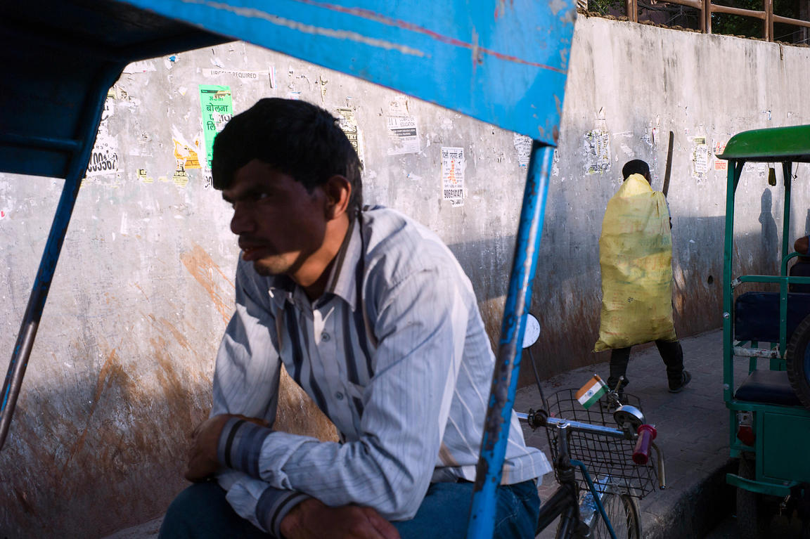 A Rickshaw Puller Awaits Customers Whilst A Refuse Collector Passes With A Yellow Sack On His Back