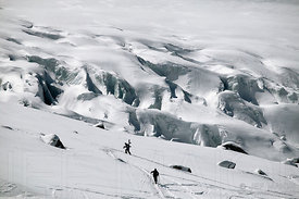Snowboarder and skier climbing slope