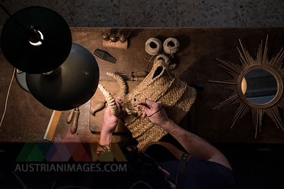 Artisan braiding a wicker bull's head in his workshop