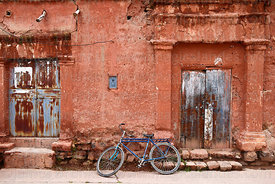 Blue bicycle propped up outside old wooden door of colonial house, Lampa, Peru