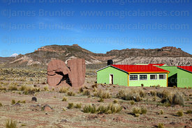 Adobe chulpa next to modern buildings on outskirts of Curahuara de Carangas, Oruro Department, Bolivia