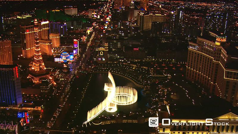 Looking down the Las Vegas Strip at night with the Bellagio's fountains in foreground.