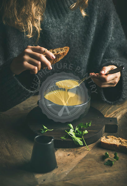 Woman in winter sweater eating sweet corn soup from bowl