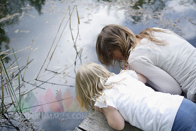 Germany, Bavaria, Mother and daughter looking into pond