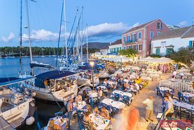 Restaurants with people eating out and harbor at night. Fiskardo, Kefalonia, Greece