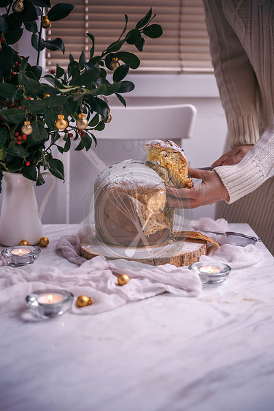 Woman slicing Panettone Christmas cake