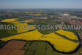 Newark on Trent aerial photograph of the fields of Rape seed in flower and the meandering course of the river Trent with Newark on Trent in the distance