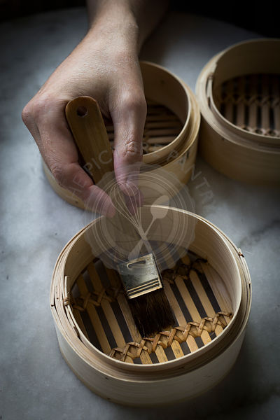 Man's hand greasing bamboo steamers on marble tabletop with a brush