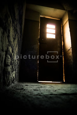 An old metal door, with a window, letting light into a damp and decaying room.