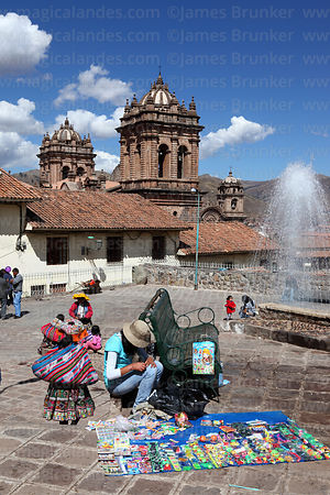 Street stall by fountain , cathedral towers behind, Cusco, Peru